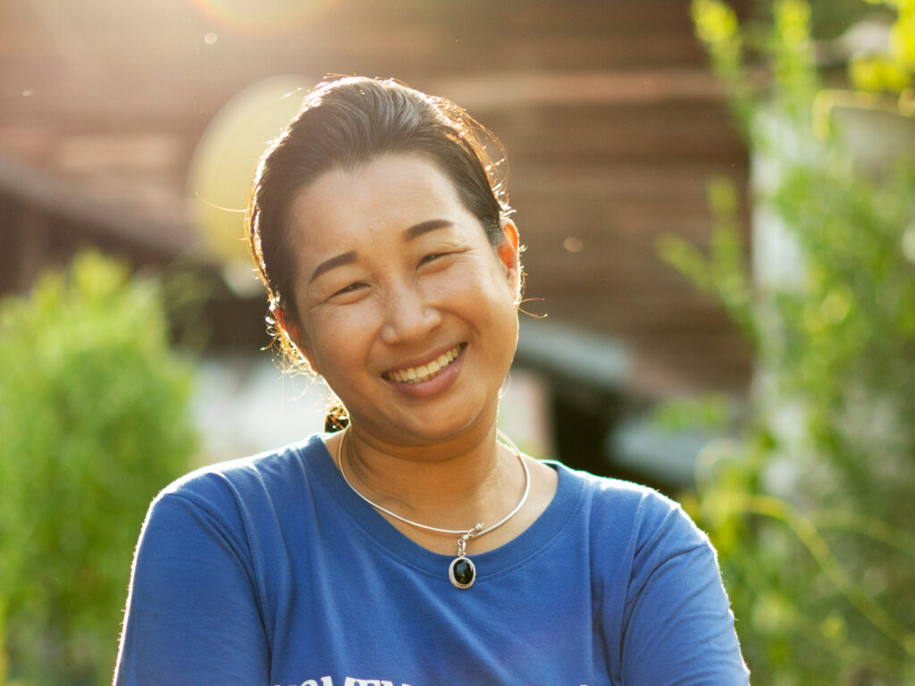 A Thai woman smiling with the sun in her back.