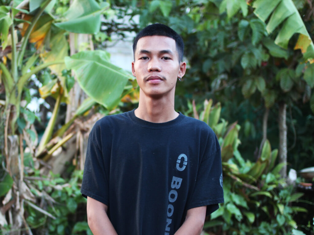 A young Thai man standing with trees behind him.