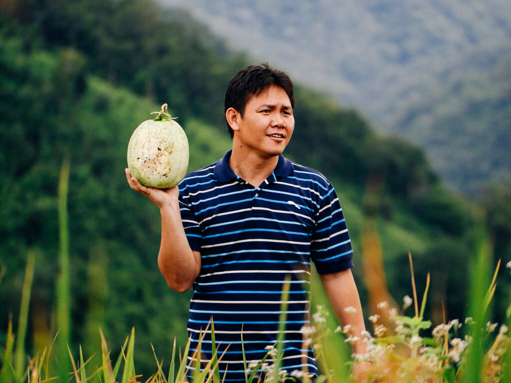 A man standing in a large dield with mountains in the background, holding a large fruit.