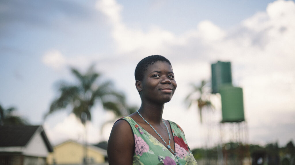 A Zimbabwean woman in sunset, looking into the camera.