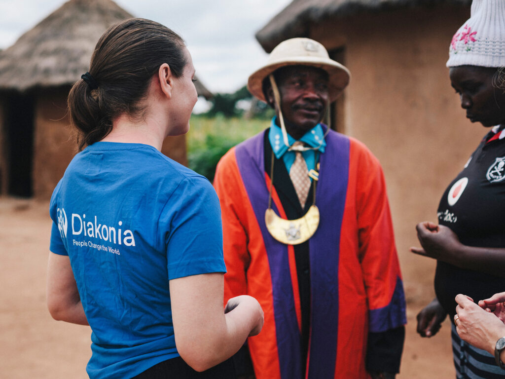 A woman with a Diakonia t-shirt with her back against the camera talking to two Zimbabwean men.