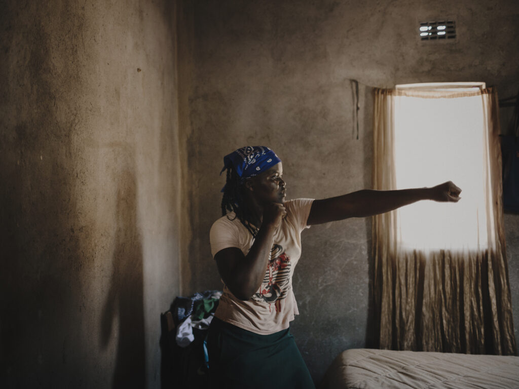 A Zimbabwean woman in a room in a boxing pose.