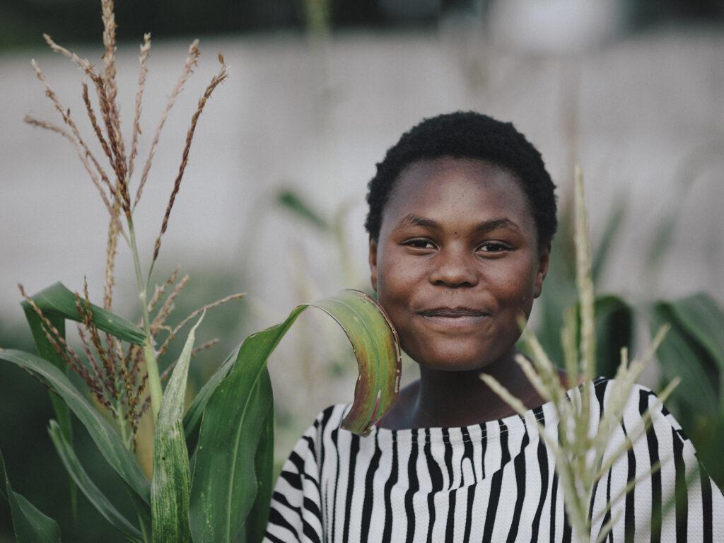 A closeup of a Zimbabwean woman in a field.