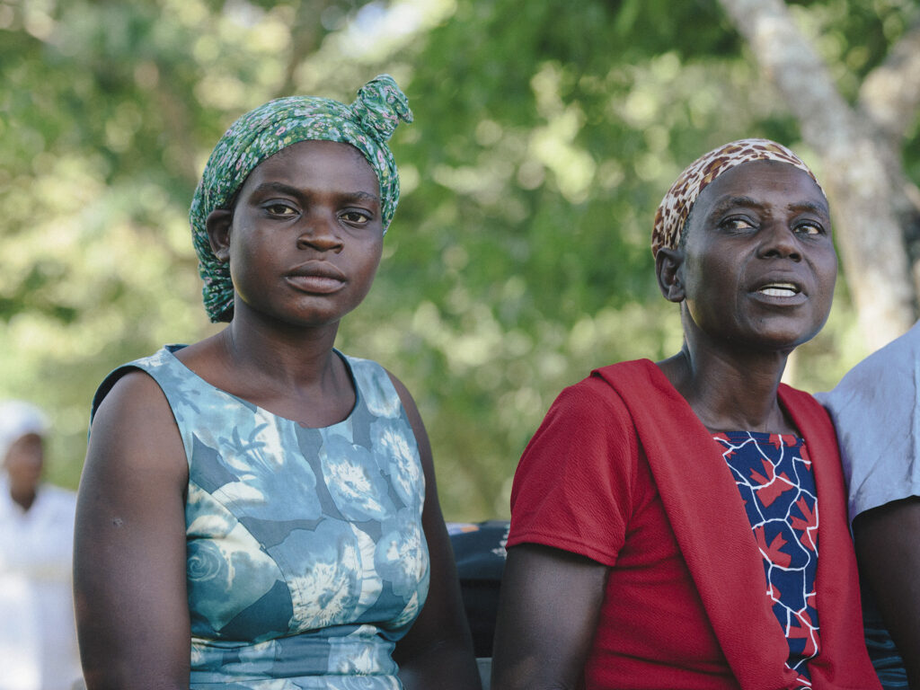 Two Zimbabwean women sitting next to each other. Behind them there are trees.