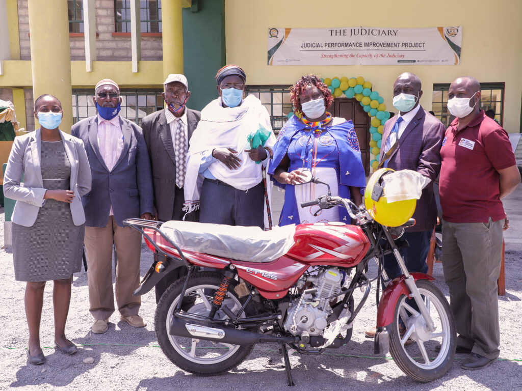 A group of people standing in front of a buidling with a motorcycle in front of them