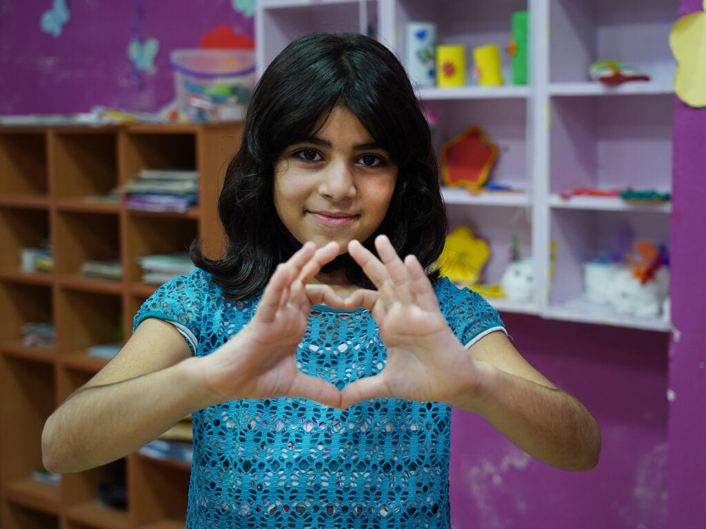 A young girl is holding up her hands to the shape of a heart.