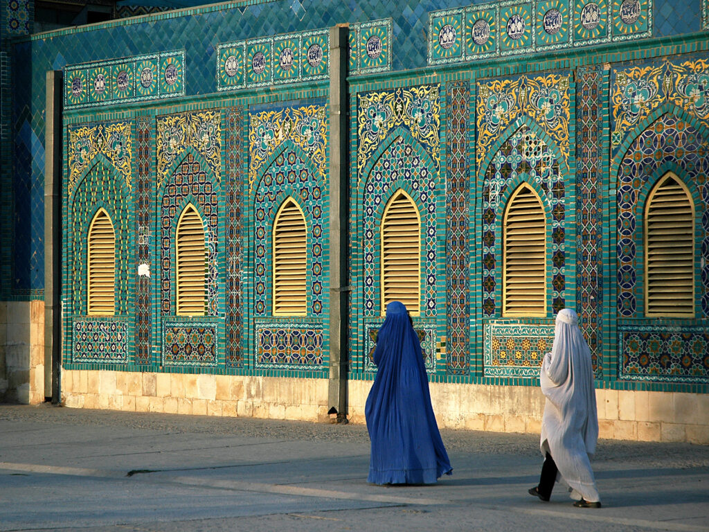 Two women wering burqas seen from behind, walking past a mosque.