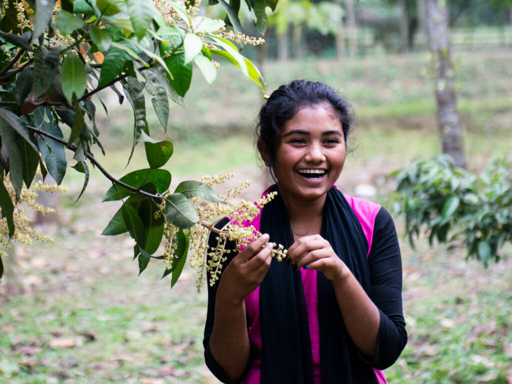 A young woman standing next to a tree, laughing.