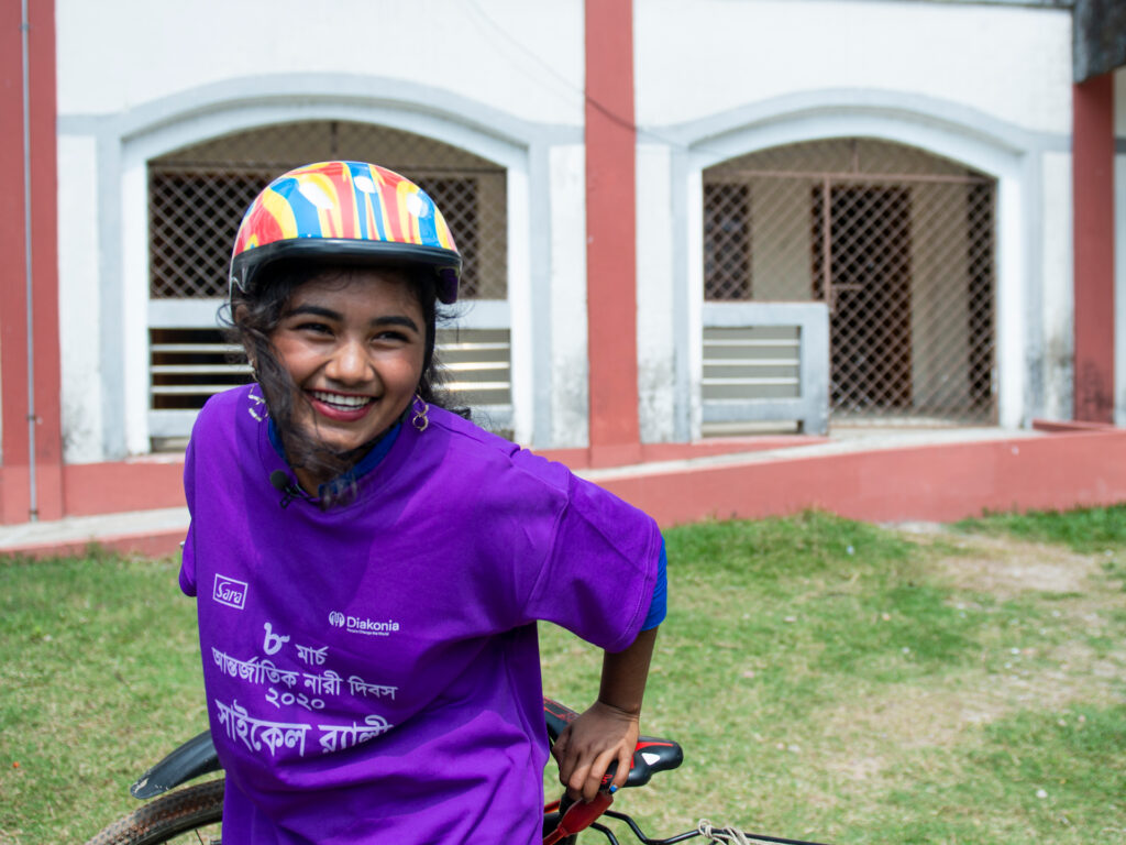 A young woman wearing a bicycle helmet and a purple t-shirt, smiling.