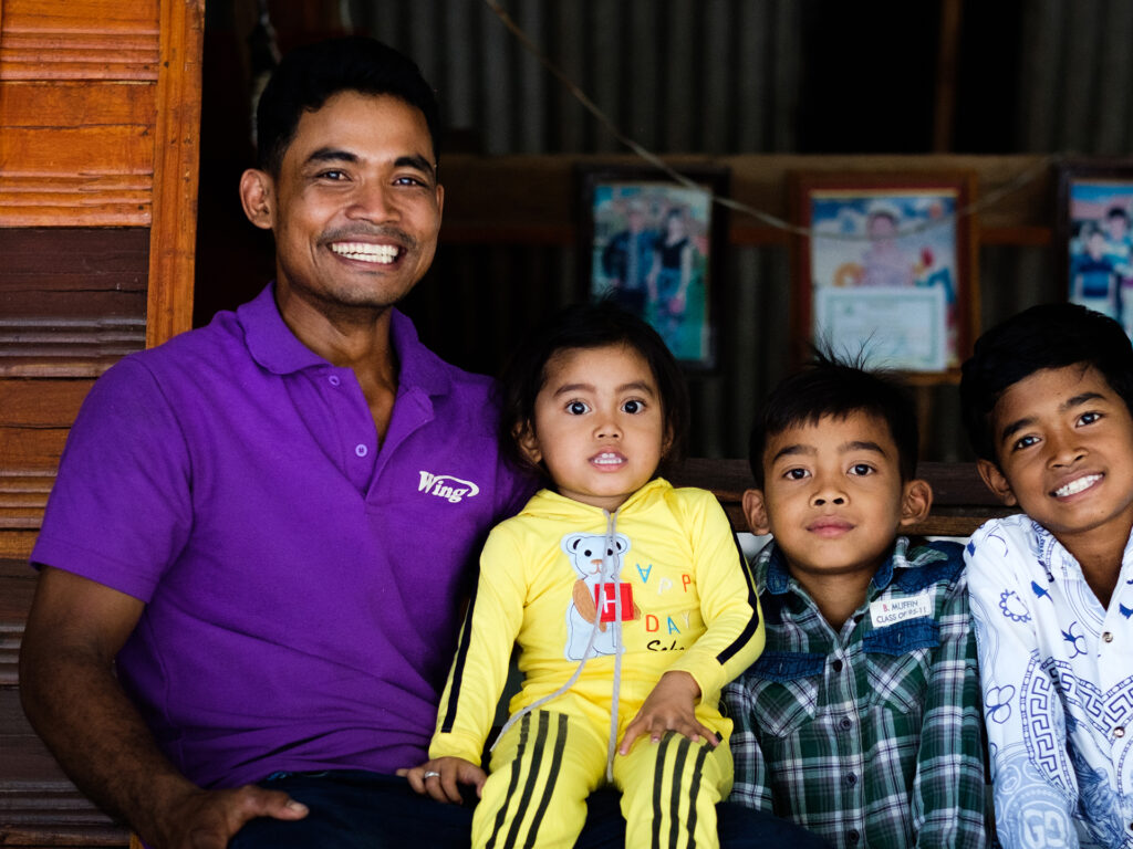 A smiling man together with three children looking in to the camera.