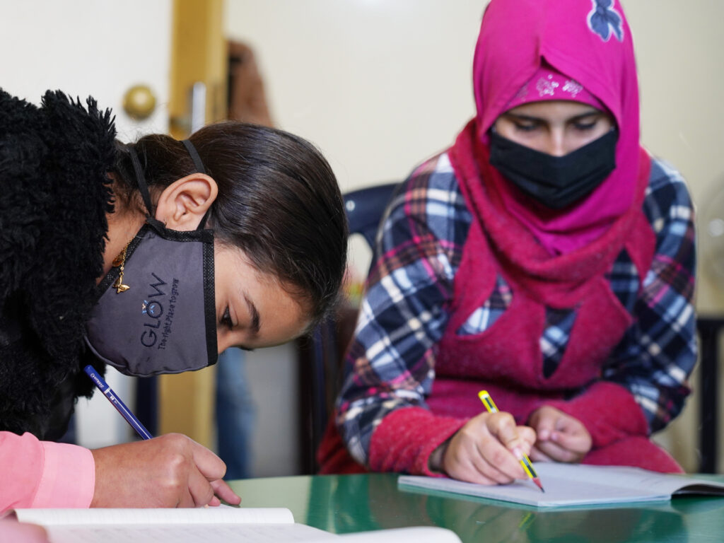 Two girls wearing face masks are leaning down into note books and writing.