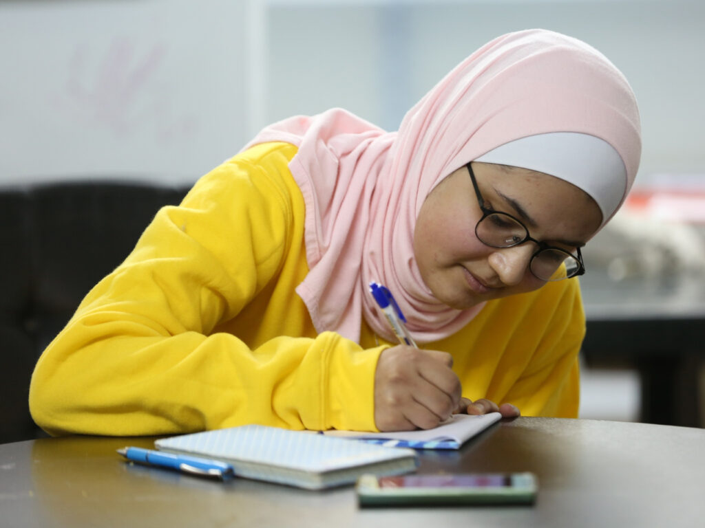 A young woman wearing a pink hijab and a yellow shirt looking down in a book and writing.