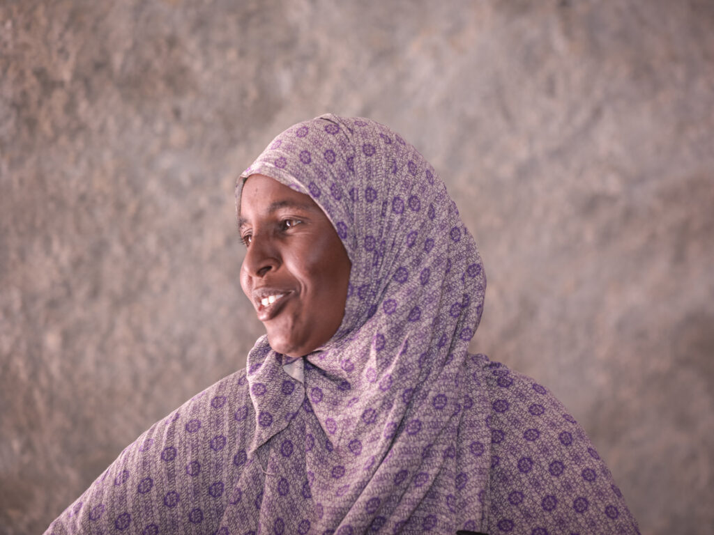 A woman in a purple hijab looking to the side and smiling.
